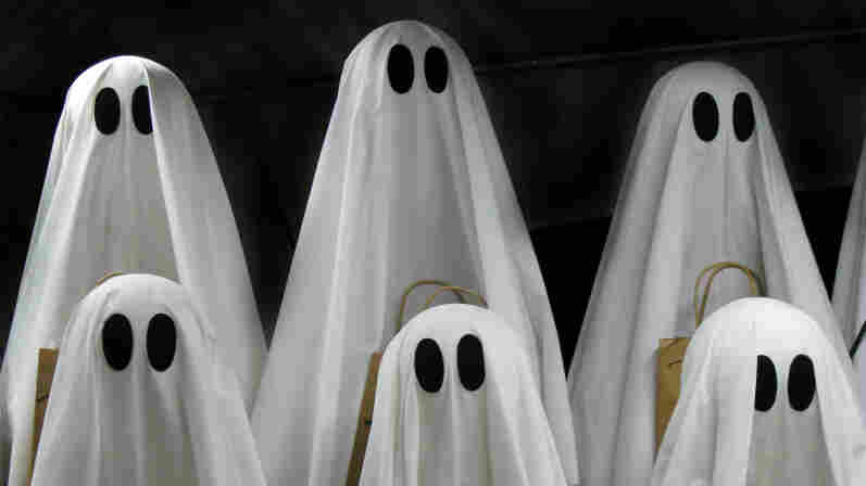 A bunch of ghosts hang out with trick-or-treat bags.