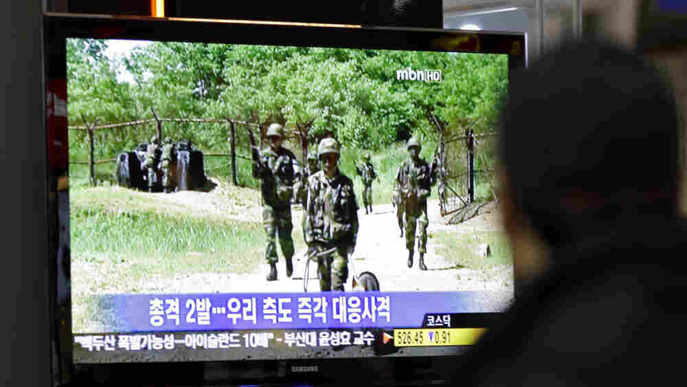 A man at a train station in Seoul watches a TV news program on the exchange of fire on the border.