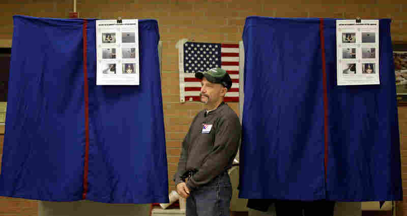 An election worker monitors a voting booth in Wilmington, Del. Democrat Chris Coons defeated Christine O'Donnell in the Senate runoff.