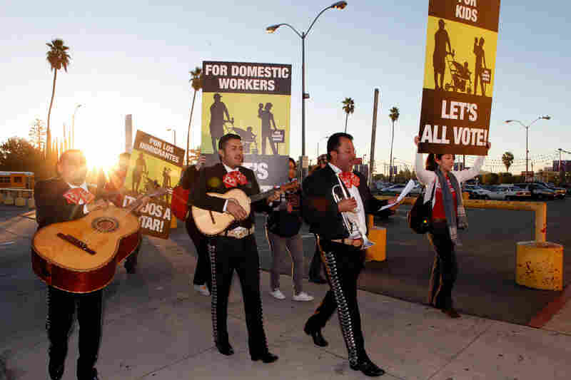 Members of the mariachi band Los Munecos and volunteers with the Coalition for Humane Immigrant Rights of Los Angeles (CHIRLA) serenade voters in North Hollywood. Advocates in Los Angeles urged immigrants to vote early.