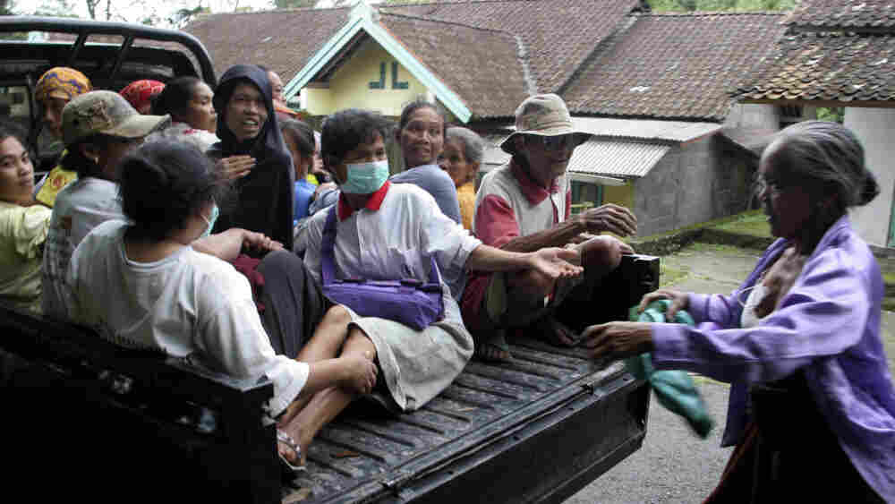 villagers board a truck as they evacuate