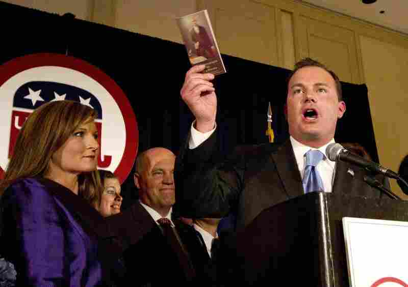 Senator-elect Mike Lee, a Tea Party-fueled upset winner in the Utah Republican primary, holds a copy of the Constitution as he celebrates Tuesday's victory over Democrat Sam Granato. He's shown with his wife, Sharon, in Salt Lake City.