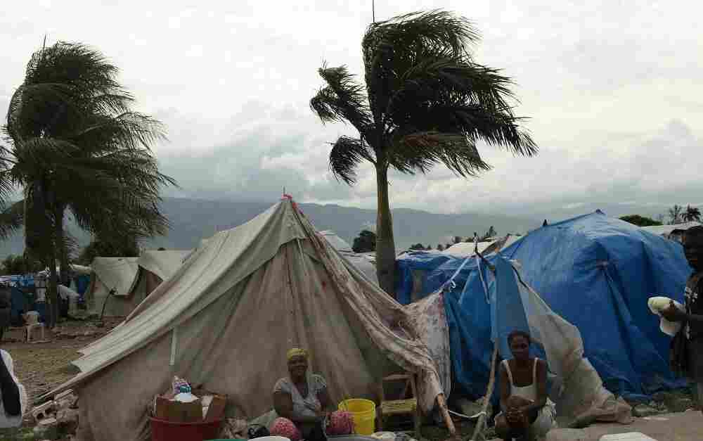 Haitian women cook outside their tent in Port-au-Prince.