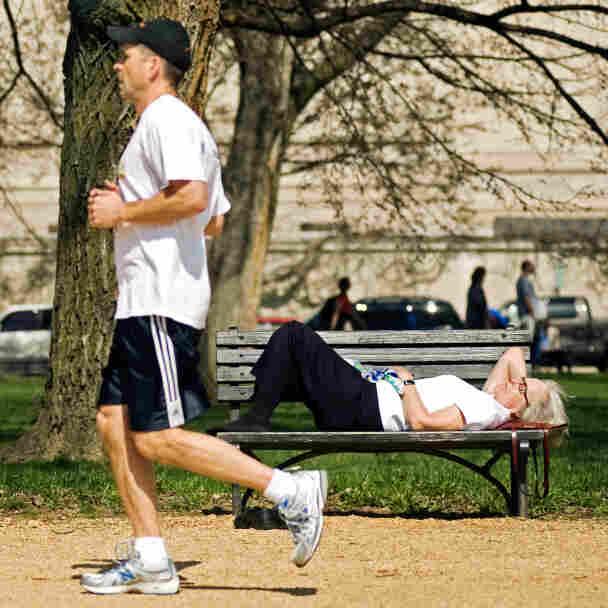 A jogger passes two women napping