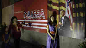 A woman makes her daughters pose for a photograph beside a poster of President Obama in Calcutta