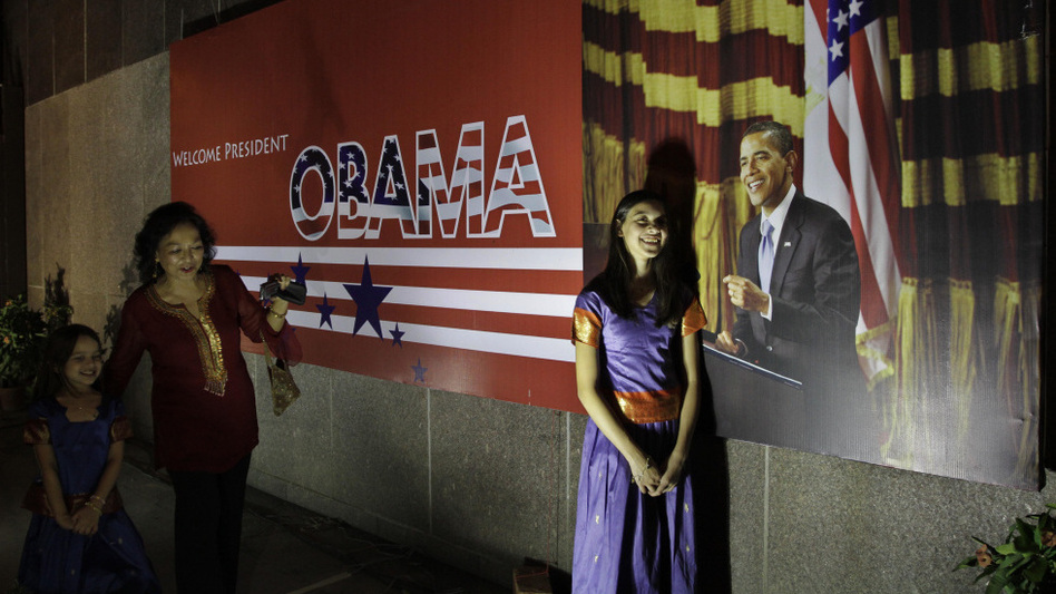 A woman makes her daughters pose for a photograph beside a billboard of U.S. President Obama in Calcutta, India, on Thursday. Obama is scheduled to arrive Friday for a four-day tour.