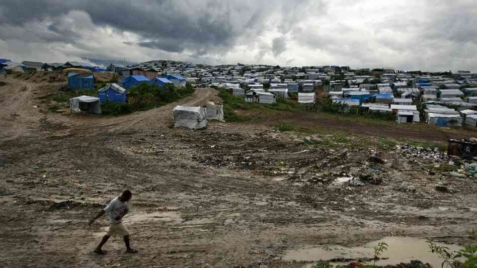 A man walks past a refugee camp