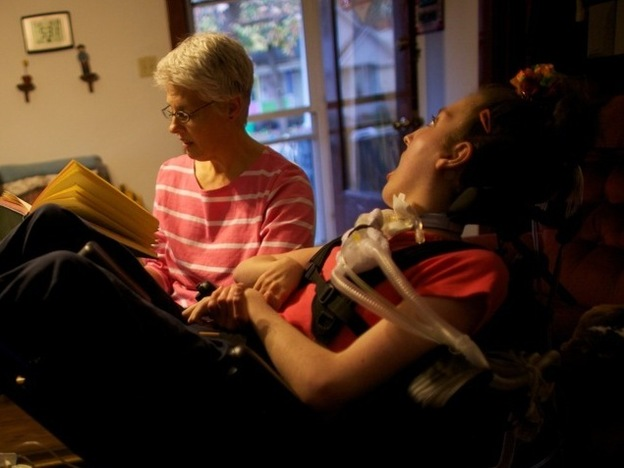 Olivia's mom, Tamara, reads to her in the family's living room in Lincoln, Ill.  Her father John and brother Brian are on the couch.   Olivia Welter is 20 years old, now. She breathes with the help of the portable ventilator on the back of her wheelchair. She can't speak. She can't move. She can't even close her eyelids--her eyes are wide open.