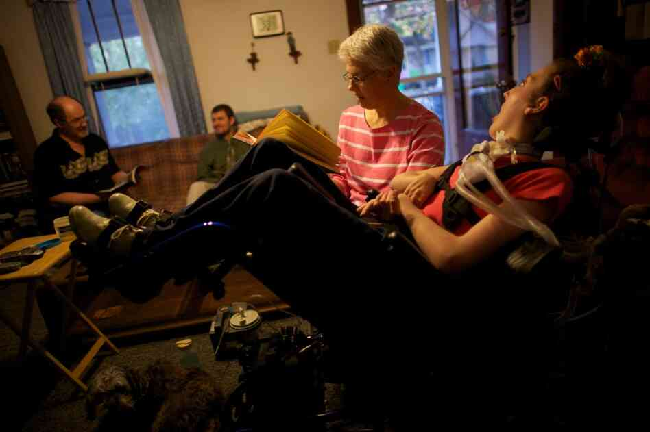 Welter's mom, Tamara, reads to her in the family's living room with her father John and brother Brian in Lincoln, Ill. Now, nurses care for Welter 16 hours a day. John and Tamara take over the other eight hours. If they lose the funding for Olivia's care, the Welters will become her round-the-clock caregivers.