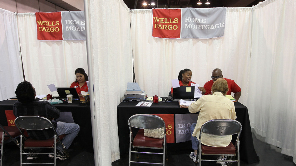 Wells Fargo employees help homeowners go over paperwork during a free workshop for customers who are facing mortgage payment challenges in Oakland, Calif.