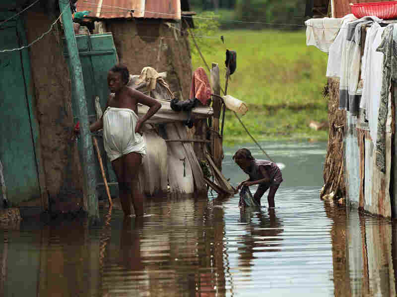 People stand outside homes in Petite Riviere, Haiti, that were flooded by Hurricane Tomas.