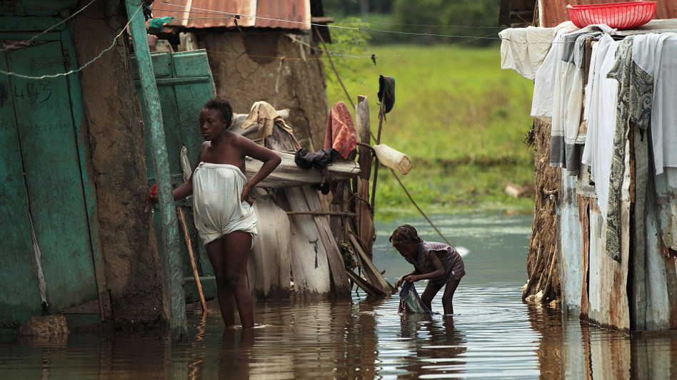 People stand outside homes in Petite Riviere, Haiti, that were flooded by Hurricane Tomas. Experts fear that cholera, a waterborne disease, could spread in crowded areas. Cholera has been confirmed in half of Haiti's 10 provinces.