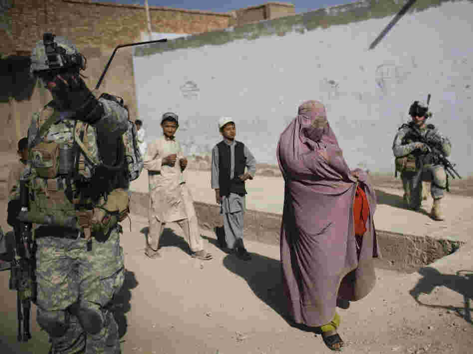 An Afghan woman walks among U.S. soldiers in Kandahar City.