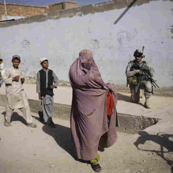 An Afghan woman walks among U.S. soldiers in Kandahar City.