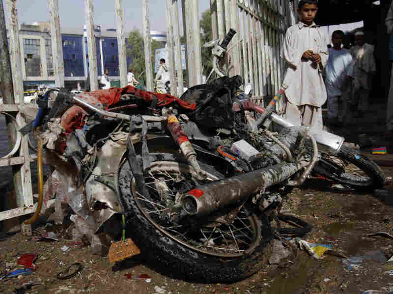 An Afghan boy stands aside a motorbike used by a suicide bomber.