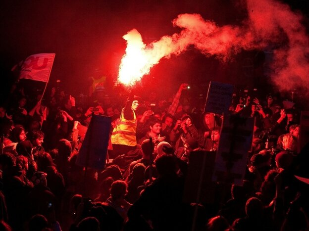 A demonstrator holds a flare during a protest outside the headquarters of the Conservative Party.