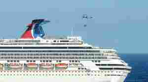 A Navy helicopter delivers pallets of supplies to the Carnival cruise ship Splendor off the coast of