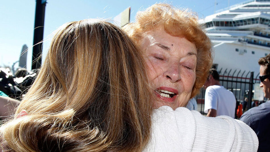 Jeanne Ralston, facing camera, gets a hug from her daughter Cindi Wolfe after disembarking. (AP)