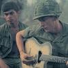 A soldier plays guitar in Vietnam.