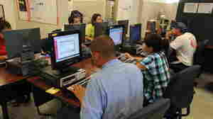 People search for jobs in an employment office in El Centro, Calif.