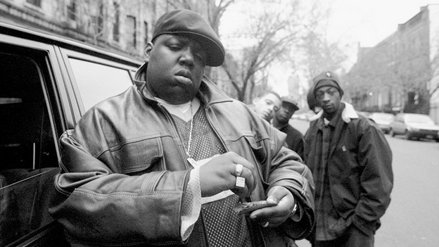 Notorious B.I.G. rolls a cigar outside his mother's house in Brooklyn in 1995. (Getty Images)