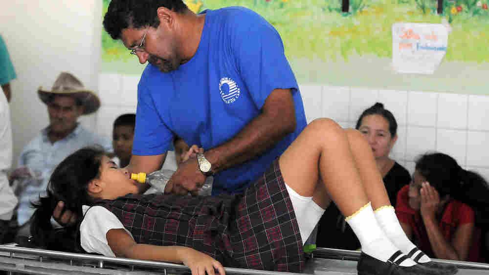 A man helps his dengue fever-stricken da