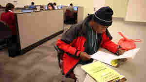 Maurice Jones looks through job listings at a career center in Oakland, Calif.