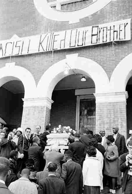 "Jackson's casket is carried into a church for funeral services on March 3, 1965, under a banner that reads ""Racism Killed Our Brother."" The death of 26-year-old Jackson galvanized civil rights leaders across the country."