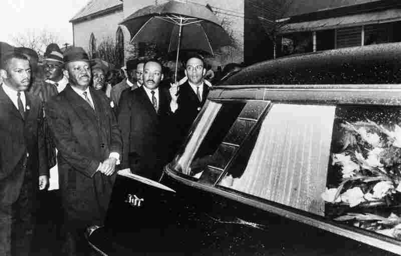Martin Luther King, Jr. (third from left) leads a procession behind Jackson's casket. King traveled to Alabama to speak at the funeral services and later led mourners three miles in the rain to a cemetery for burial.