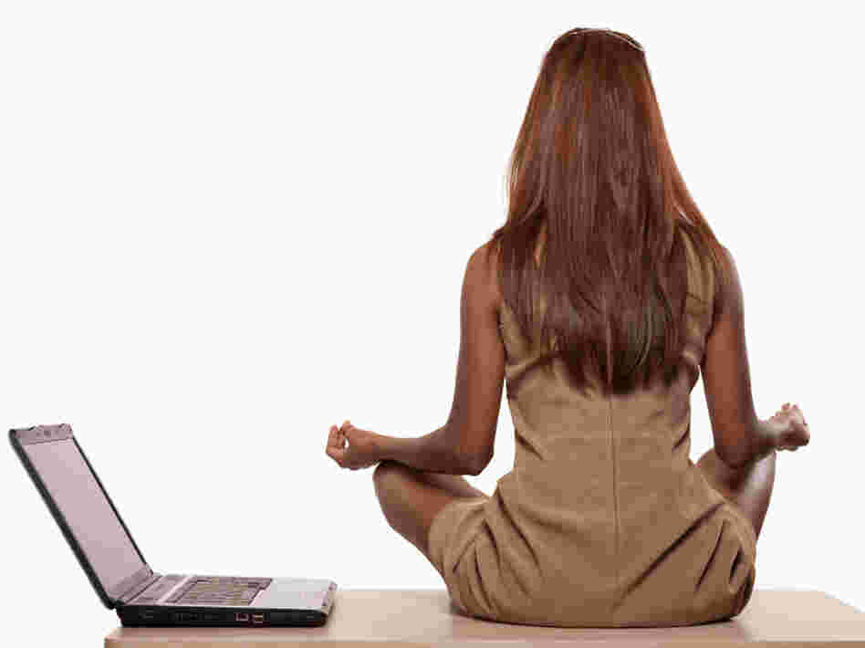 Woman performs yoga next to her open laptop.