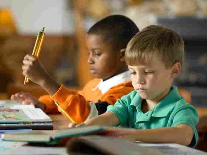 Two boys learn to read in school