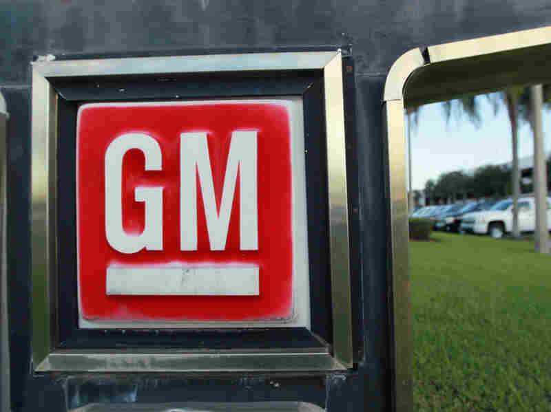 A GM sign near an automobile sales lot.
