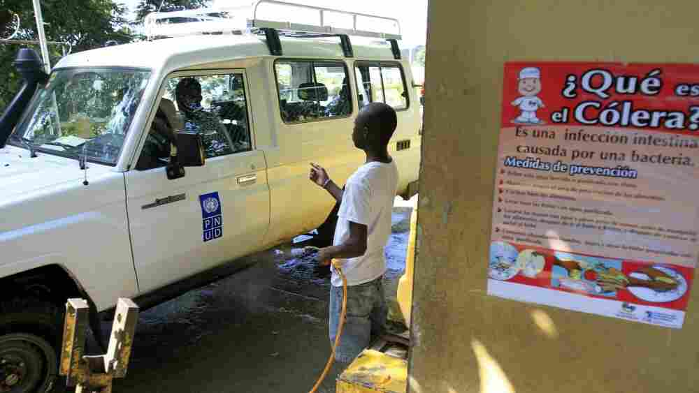 A Public Health civil servant disinfects the vehicles coming into the Dominican Republic from Haiti.