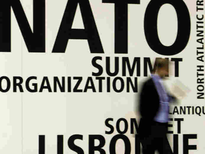 A man walks by NATO's summit venue in Lisbon.