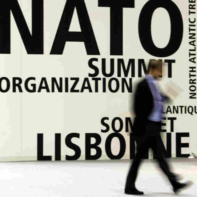 A man walks by NATO's summit venue in Lisbon.
