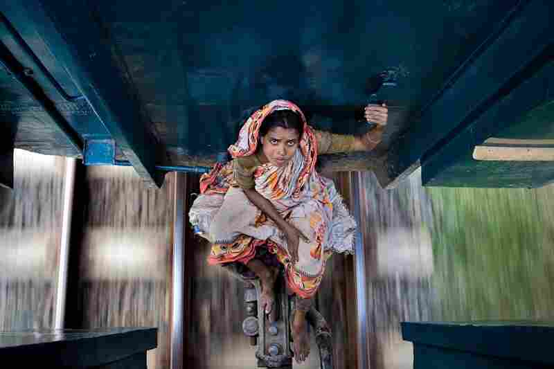 During Ramadan, a woman rides between the railway carriages of a train heading north from Dhaka, the capitol of Bangladesh.