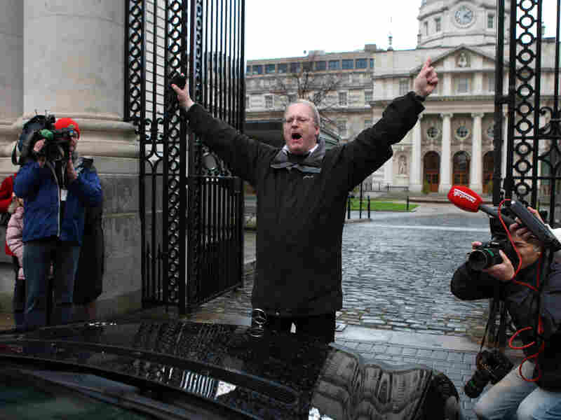 A protester stops a car carrying an Irish official arriving for a cabinet meeting in Dublin.