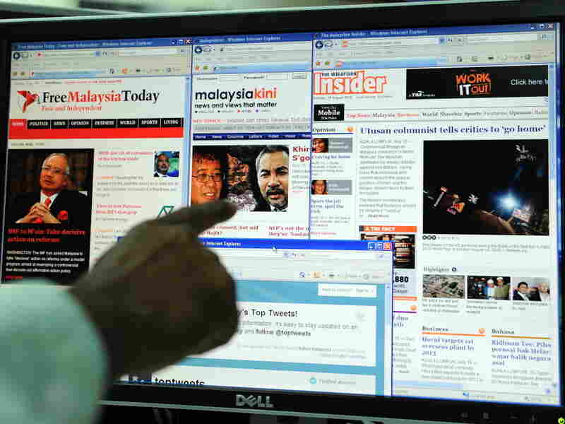 A computer user in Kuala Lumpur points to local news portals on the Internet.