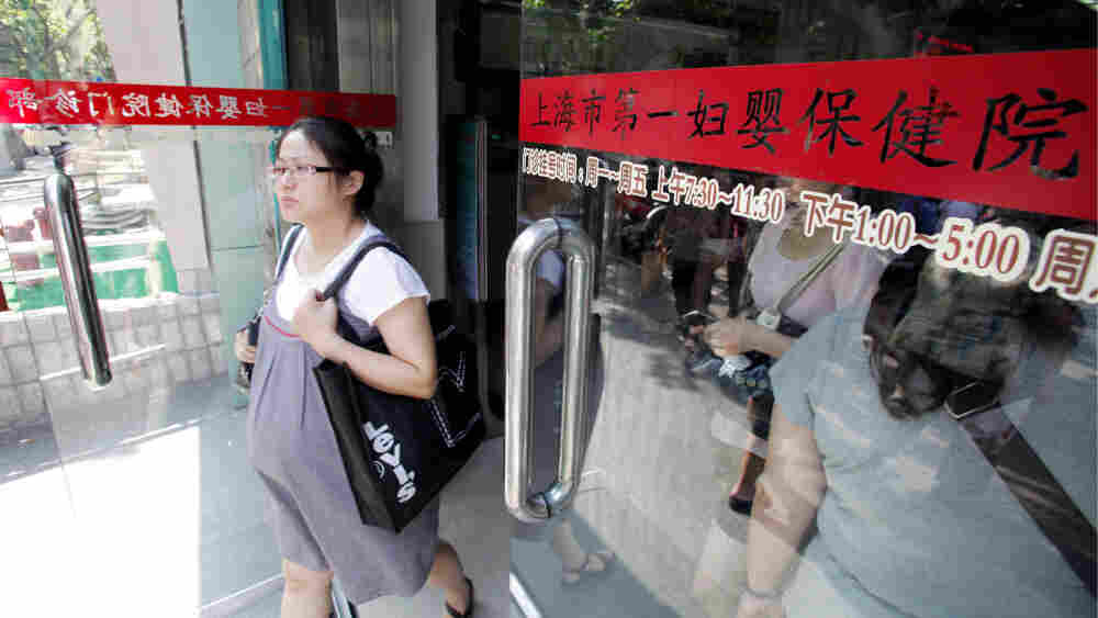 A pregnant Chinese woman walks out of a hospital in Shanghai in August 2010