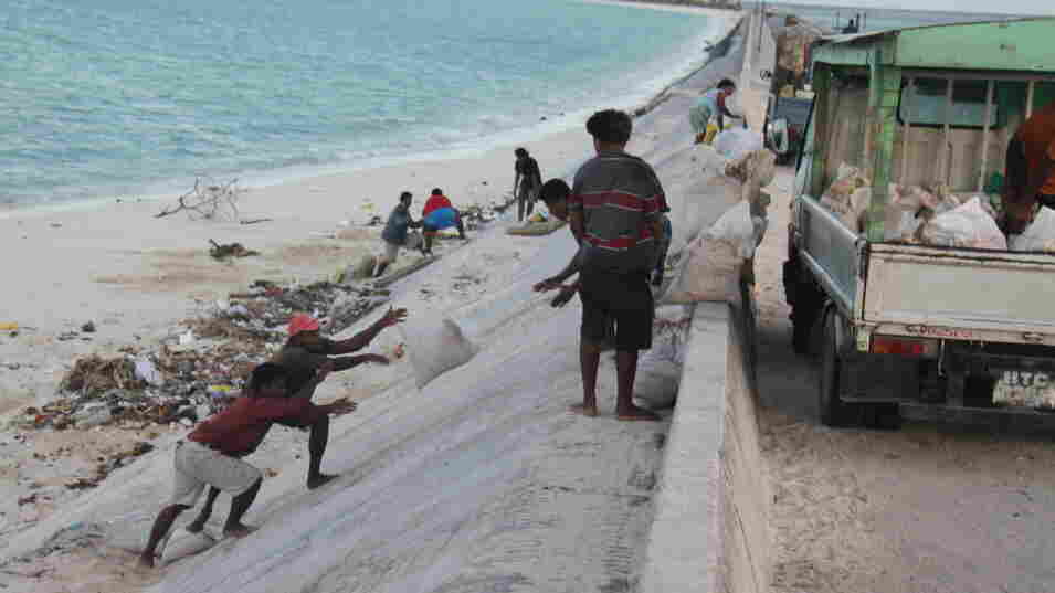People mine bags of sand along a causeway in South Tarawa.