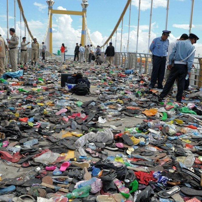 Cambodian police officials examine hundreds of shoes and other belongings left behind on a bridge in