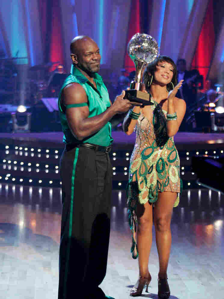 Dancers Emmitt Smith and Cheryl Burke celebrate their win and display the mirrorball trophy.