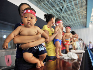 Hundreds of Chinese babies prepare to participate in a swimming contest in September in Beijing. In China, children with no siblings often find concession difficult to deal with, since their parents traditionally give in to their demands.