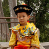 "A Chinese family coaxes their son to pose in a ""little emperor"" costume at a Beijing park"