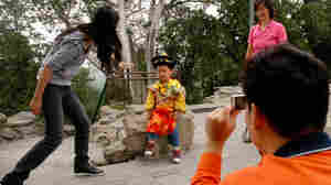 """A Chinese family coaxes their son to pose in a """"little emperor"""" costume at a Beijing park"""