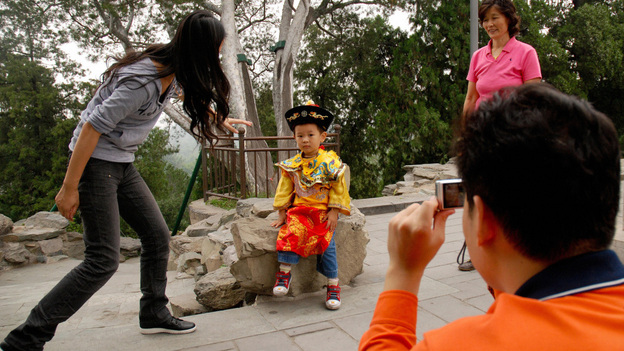 A Chinese family coaxes their son to pose in a