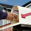 A letter carrier delivers a bundle of mail to a mailbox