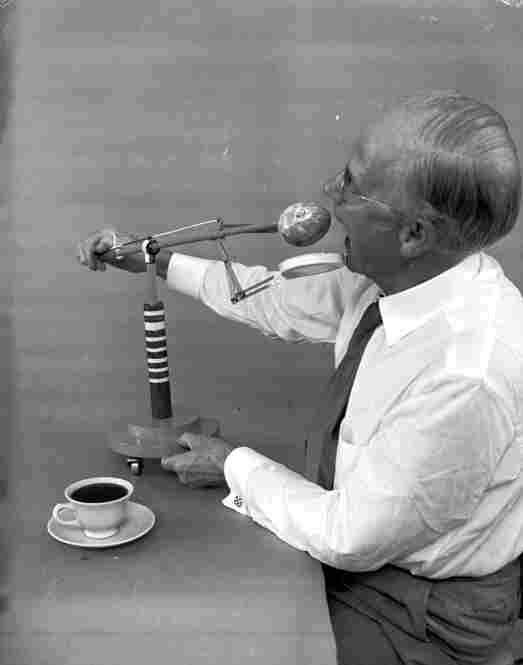 American amateur inventor Russel E. Oakes demonstrates his doughnut dunker, which prevents doughnuts from dripping and wetting the diner's fingers, heaven forbid.