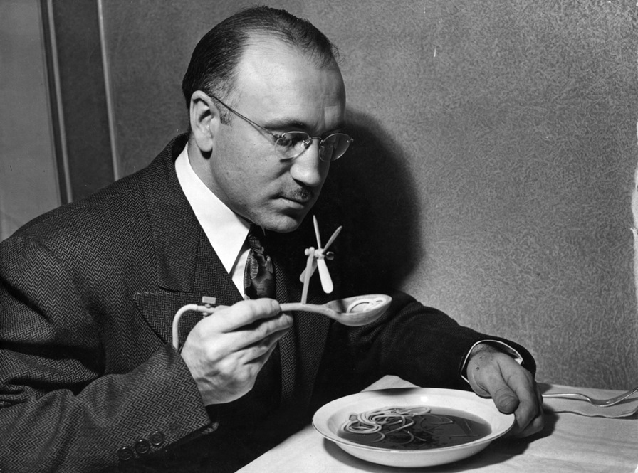A man eating soup with a mechanical soup spoon. The device is intended for dinner parties where the hostess serves inedible soup. The offending soup is drained through a hollow handle, via a tube hidden up the sleeve, into a bottle attached to the leg. Foul odours are blown away by the propeller. The innocent hostess believes the device is simply for cooling her delicious fare. (Hans Reinhart/K...