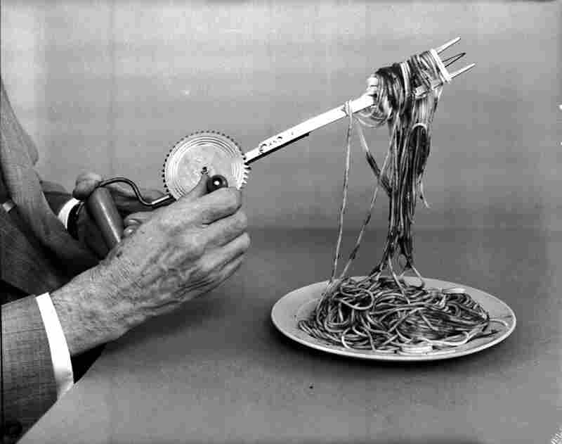A wind-up spaghetti fork in operation, devised by Oakes. The fork winds spaghetti strands making them easy to eat.